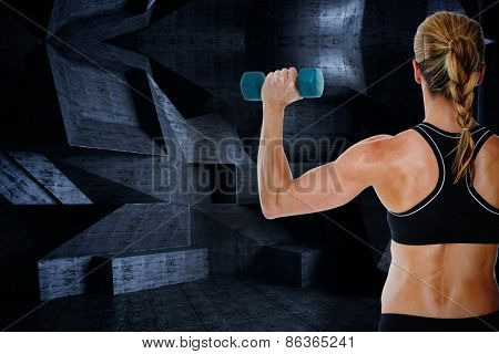 Female bodybuilder holding a blue dumbbell against dark room