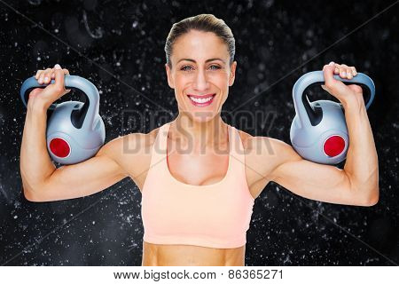 Happy female crossfitter lifting kettlebells looking at camera against black background