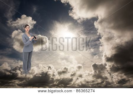 Curious young businesswoman posing with binoculars against dark sky with white clouds