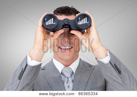 Businessman holding binoculars against grey vignette