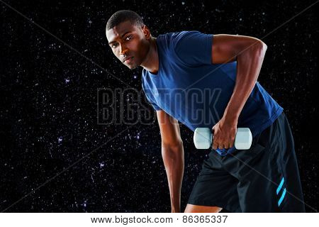 Portrait of casual young man lifting dumbbell against black background
