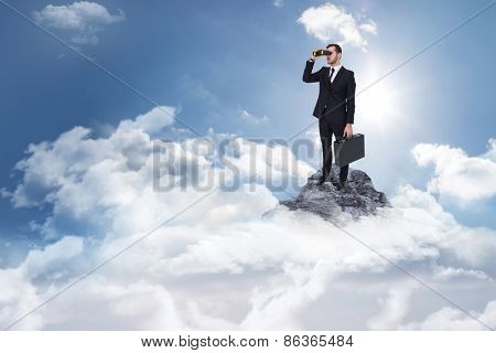 Businessman holding a briefcase while using binoculars against mountain peak through the clouds
