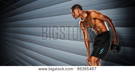 Shirtless fit young man holding barbell weight against grey shutters