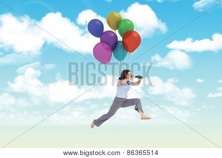 Cheerful classy businesswoman jumping while holding binoculars against blue sky