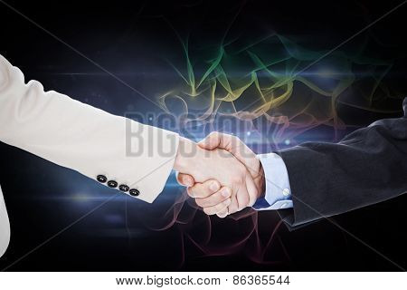 Smiling business people shaking hands while looking at the camera against black background with spark