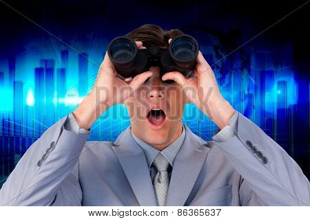 Suprised businessman looking through binoculars against blue bar chart graphic with light