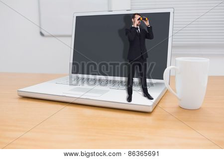 Elegant businessman standing and using binoculars against a desk with a computer