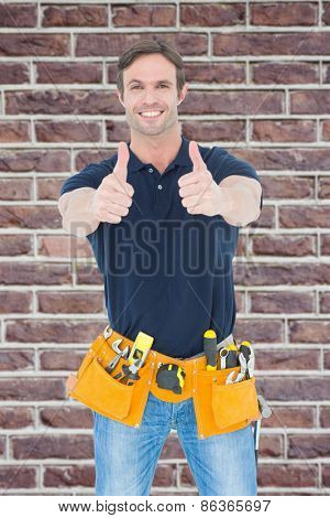 Man wearing tool belt while showing thumbs up sign against red brick wall