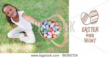 easter egg hunt graphic against little girl sitting on grass showing basket of easter eggs to camera