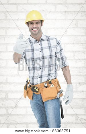 Male handyman gesturing thumbs up sign against white wall