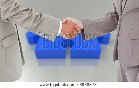 Side view of shaking hands against jigsaw