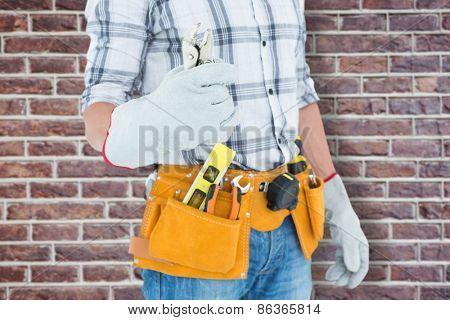 Technician with tool belt around waist holding pliers against red brick wall