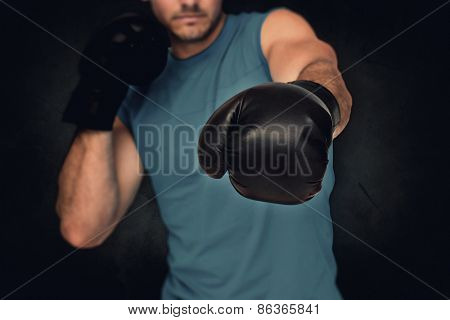 Close-up of a determined male boxer focused on training against dark background