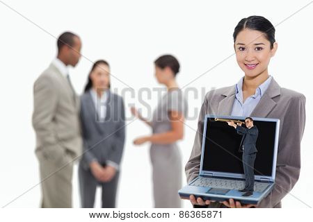 Businessman looking through telescope against businesswoman smiling showing a laptop screen with coworkers in the background