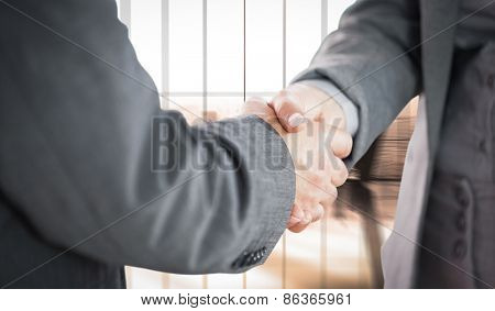 Business people shaking hands close up against room with large window looking on city
