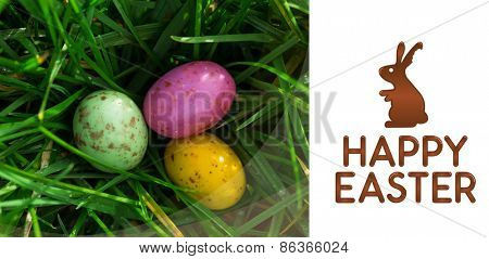 happy easter graphic against small easter eggs nestled in the grass
