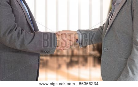 Close up on two businesspeople shaking hands against room with large window looking on city
