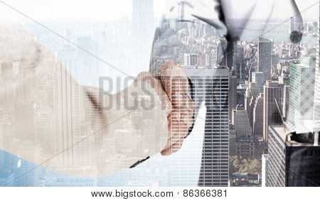 People in suit shaking hands against city skyline