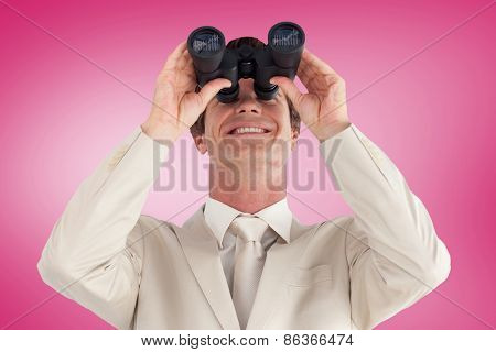 Confident businessman with binoculars against pink vignette
