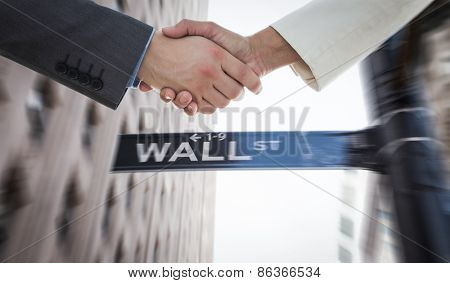 Shaking hands over eye glasses and diary after business meeting against wall street