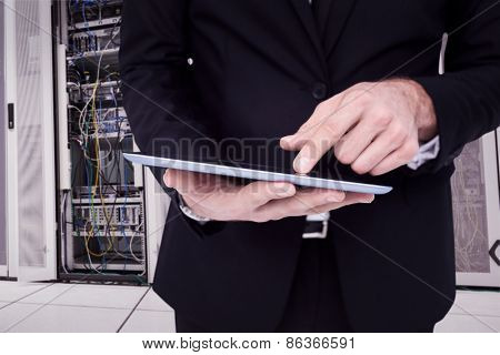 Mid section of a businessman touching digital tablet against data center