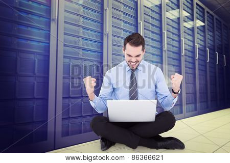 Businessman sitting with his laptop cheering against server room