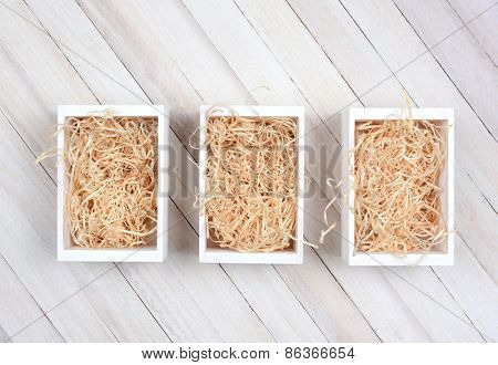 High angle shot of three wood crates filled with straw on a rustic wood table. Horizontal format with copy space.
