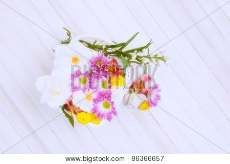 Basket of Spring flowers on a wood table. Overhead shot with intentional high key effects applied. Horizontal format with copy space.
