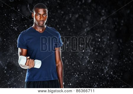 Portrait of a casual man lifting dumbbells against black background