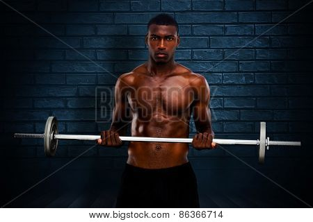 Fit man lifting barbell against black background