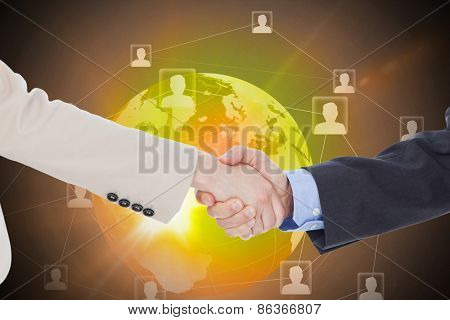 Smiling business people shaking hands while looking at the camera against global technology background