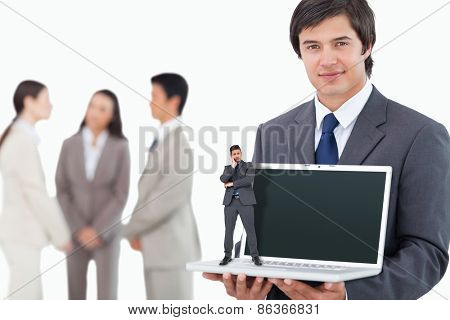 Thinking businessman against salesman showing laptop screen with colleagues behind him