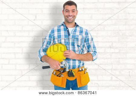 Smiling handyman holding hardhat and hammer against white wall