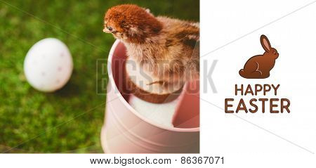 Happy Easter greeting against stuffed chick in pink bucket