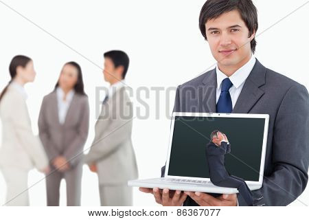 Businessman sitting against salesman showing laptop screen with colleagues behind him