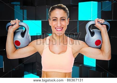 Happy female crossfitter lifting kettlebells looking at camera against blue and black tile design