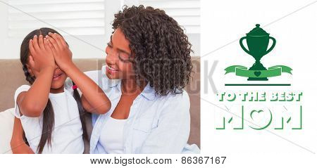 mothers day greeting against pretty mother sitting on the couch with her daughter covering her eyes
