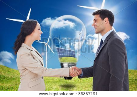 Future partners shaking hands against light bulb showing solar panels and turbines in a field with wind turbines