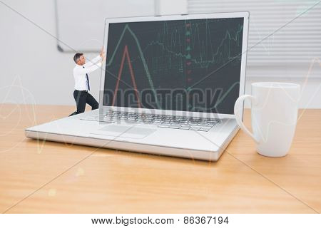 Businessman pushing against stocks and shares on black background