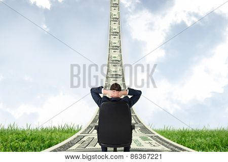 Businessman sitting in swivel chair against field and sky