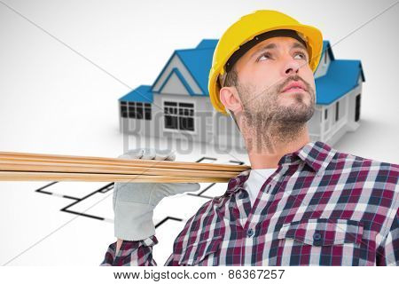 Handyman holding wood planks against blue house behind an architectural plan