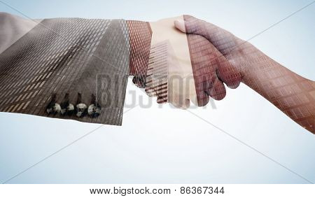 Close up of female and male hand shaking against low angle view of skyscrapers