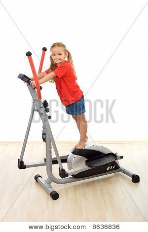 Little Girl Standing On Top Of Elliptical Trainer