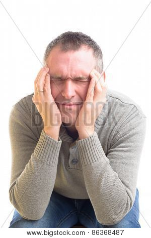 Sitting man with a headache over white background