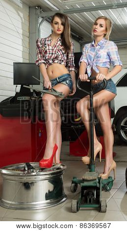 two girls mechanic replace tires on wheels
