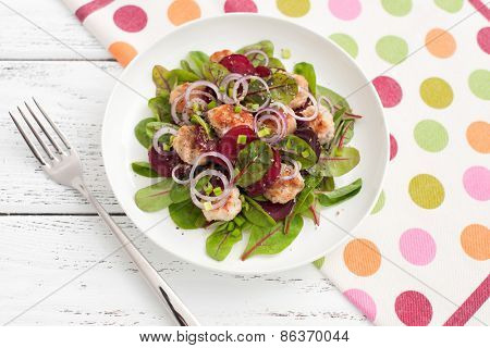 salad with lettuce, beetroot, chicken meat, green onions on wooden background.