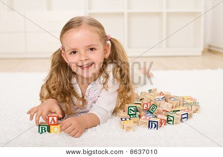 Little Girl With Alphabet Wooden Blocks Playing