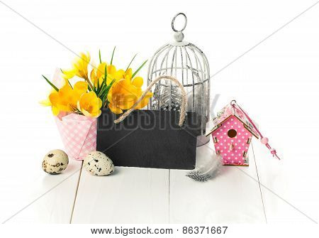 Easter Decoration With Quail Eggs, Birdcage, Yellow Spring Crocus, And Blackboard
