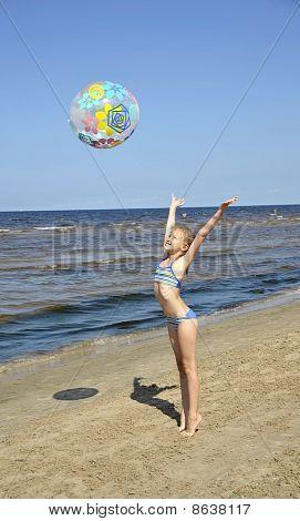The girl plays with a ball on seacoast a beach