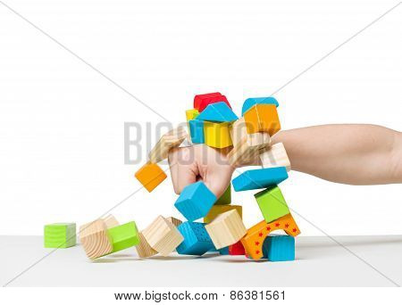 Hand Destroying House Made Of Color Wooden Blocks